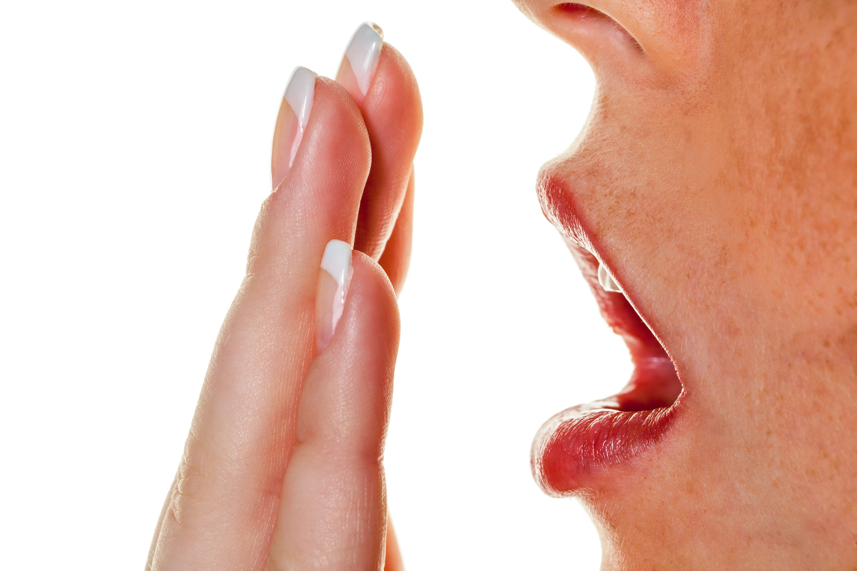 a young woman holds in her hand to her mouth to sneeze. halitosis and bad breath